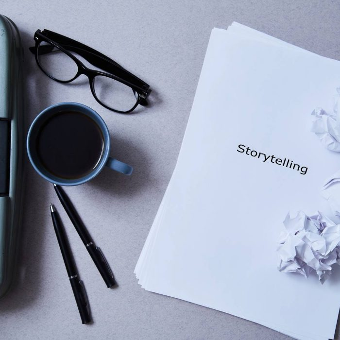 arial view of a typewriter, cup of coffee, pens, eyeglasses and a stack of papers with the word storytelling visible